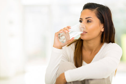 Woman drinking glass of water. Is your skin dry or just dehydrated? CloudCloth explain how to restore balance