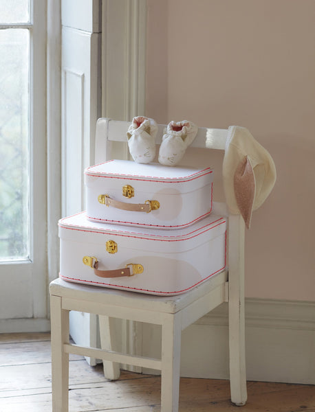 Cat baby booties by Meri Meri on top of a stack of suitcases with baby accessories