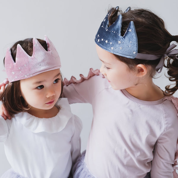 Two little girls wearing velvet crowns with silver stars and silver tie ribbons.