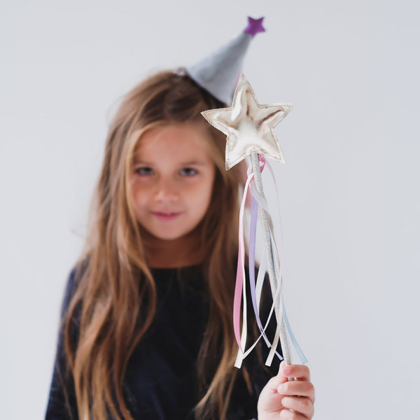 Little girl with long hair wearing a party hat and holding the Mimi & Lula pastel rainbow wand