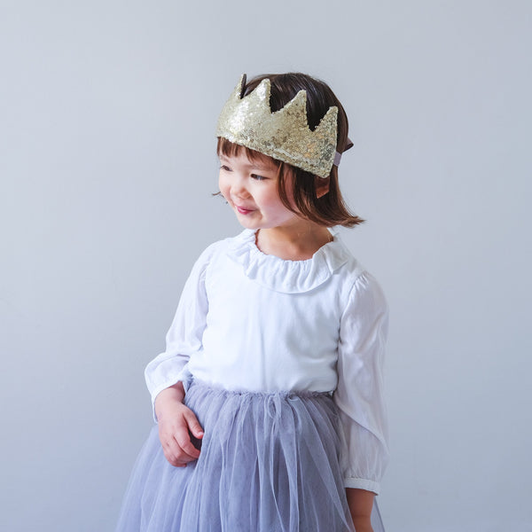 Little girl playing dressing up wearing a tutu and gold sequin crown.
