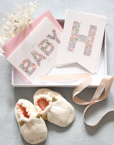 New baby girl gift box including Liberty print bunting, baby booties and new baby card from The Charming Press.