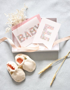 New baby gift box including greetings card, cat baby booties and Liberty print nursery decor.