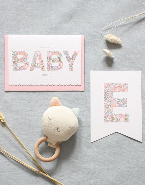 New baby gift card,  personalised Liberty print flag and cat rattle. Content of new baby girl gift box by The Charming Press.
