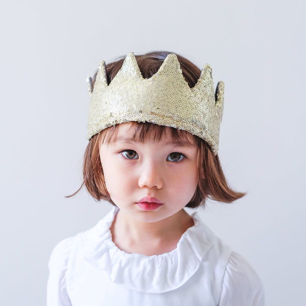 Little girl wearing Mimi & Lula gold sequin dressing up crown.