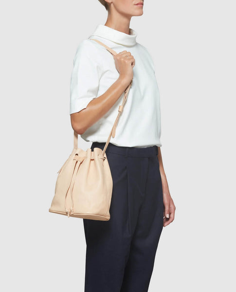 Modeling beige bucket bag