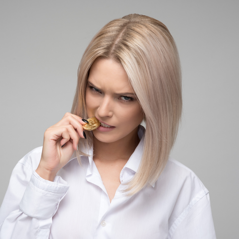 woman biting gold coin