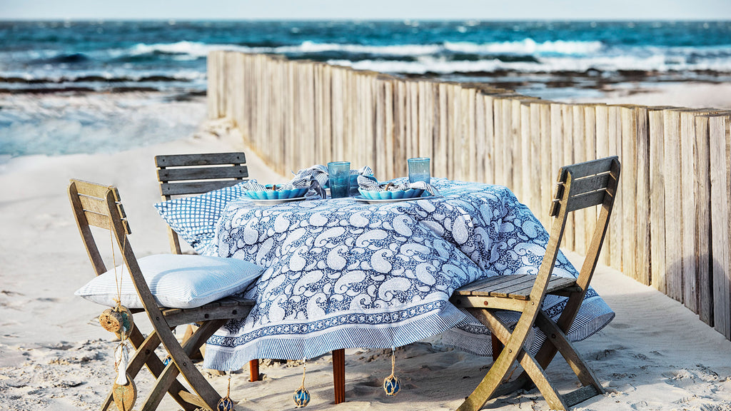Table on the beach set with a navy blue tablecloth with paisley pattern from Chamois