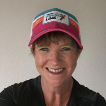 woman wearing pink technical trucker hat
