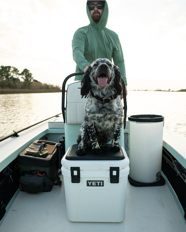 Guy enjoying a chilly morning boat ride with his dog, who sits upon a YETI cooler with his nose to the wind, looking like a true first mate!