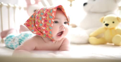 Baby in a head scarf playing on a Baby Play Mat with teddy bear soft toys