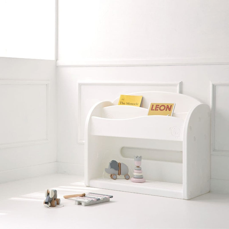 White bookshelf for kids storing children books and toys in a room with white walls.