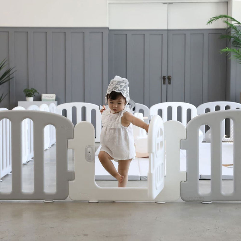 Baby play yard in white and grey which features a door with lock to keep baby safe.