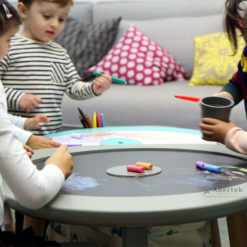 Children drawing on a multi-functional kids table with blackboard and whiteboard.