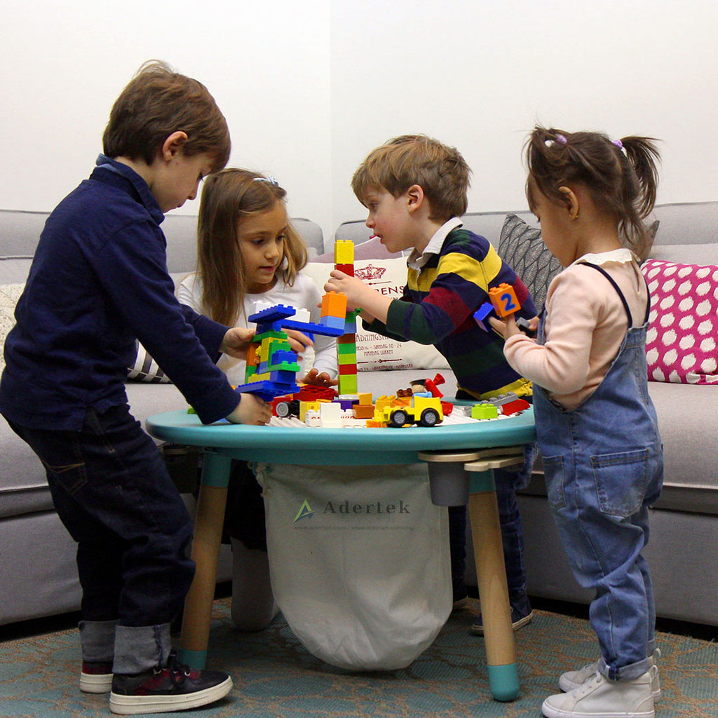 4 Kids playing with toy bricks on a table designed for kids