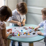 3 Children playing lego bricks on a kids table.