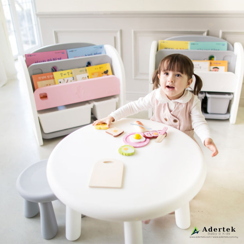 Toddler girl sitting on a kids chair playing with toys on toddler table.