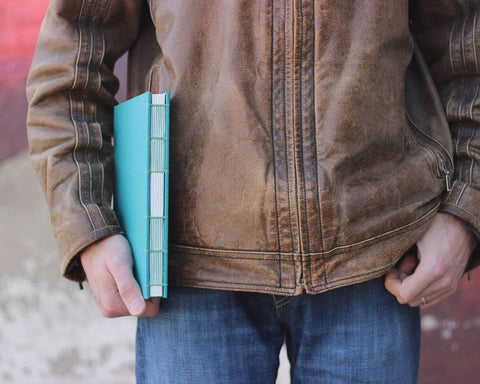 man holding teal sketchbook