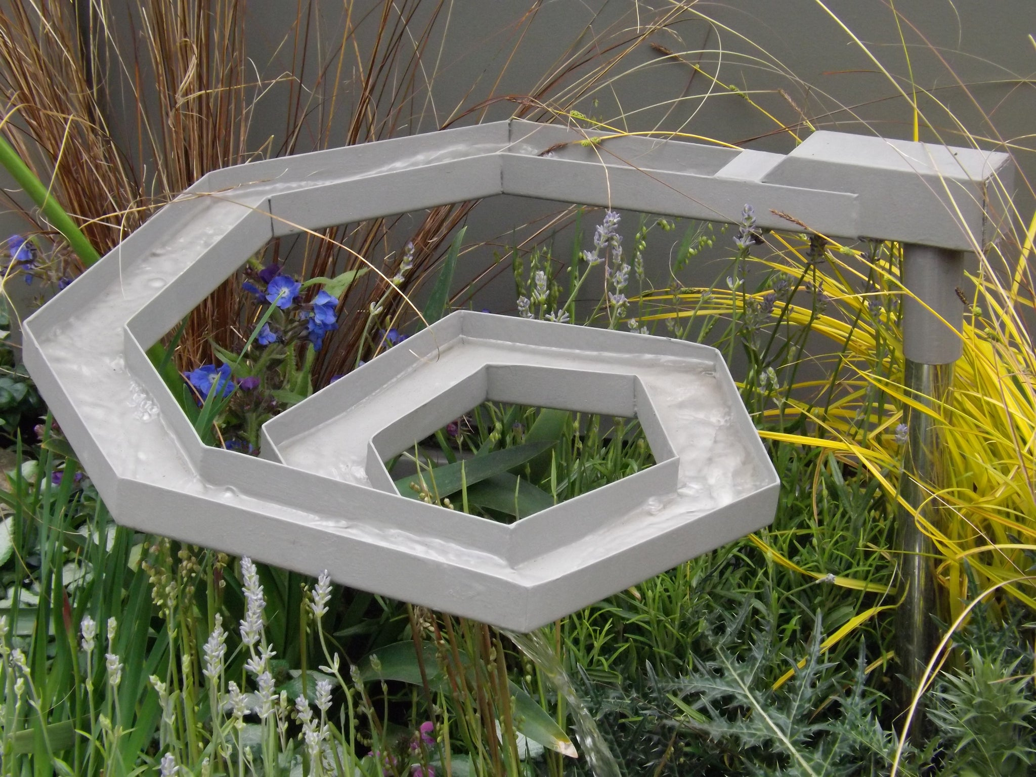 A spiral rill echoes the angular metal elsewhere in the garden