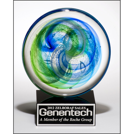 Art glass disk with blue and light green accents on black glass base with felt bottom.