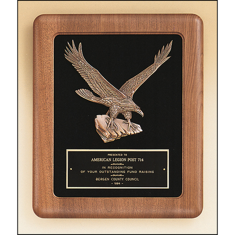American walnut frame with a sculptured relief eagle casting on a black velour background.