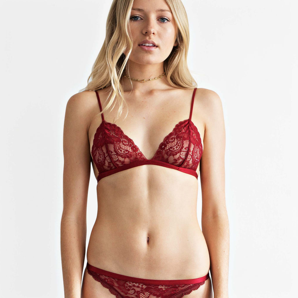 front view on model. Sheer red lace triangle soft bra