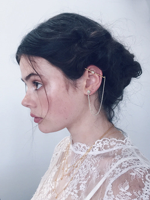 beautiful girl wearing statement gold opal ear cuff bar and fine white lace top