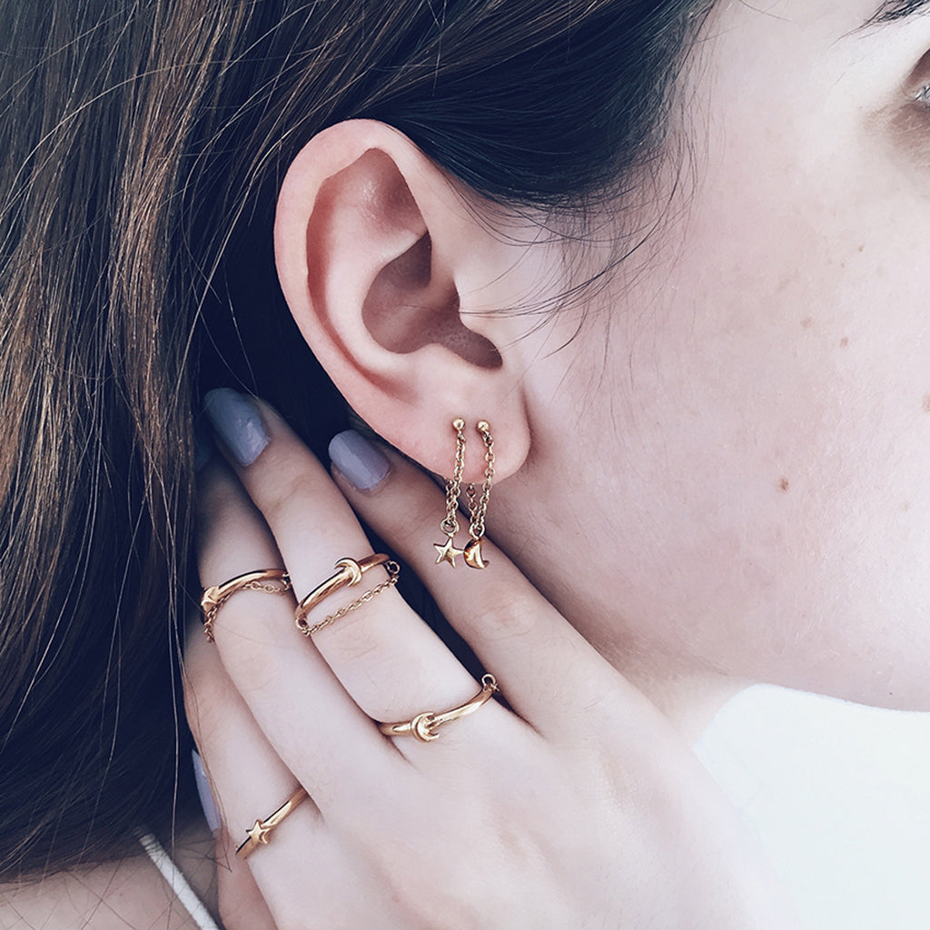 star moon dangling chain earrings in gold adorning ear lobes. mix and match back with star moon gold stacking chain rings