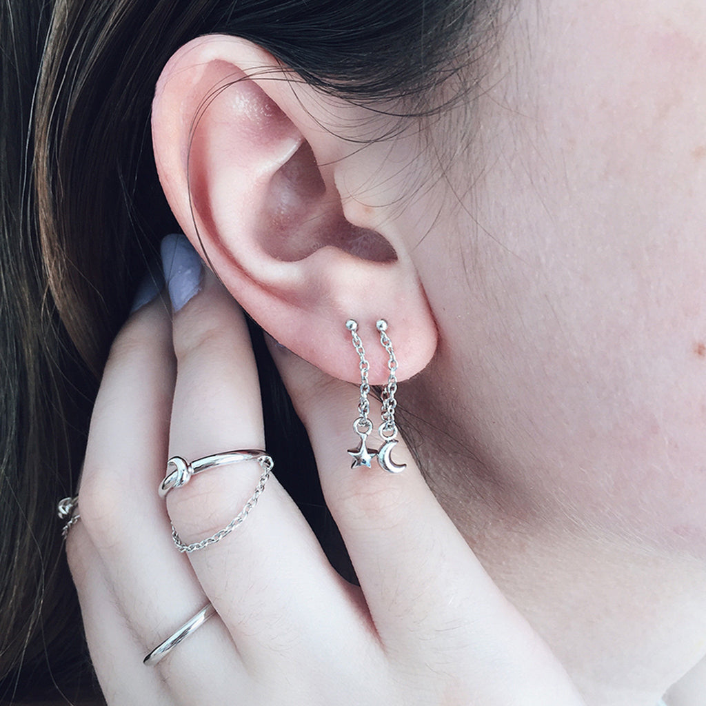 star moon dangling earrings in silver adorning ear lobes. a tiny star and moon hangs on a fine chain in this simple fashionable earring design. for the earring lover of beautiful earrings and womens jewellery, great as xmas and valentine gifts and birthday