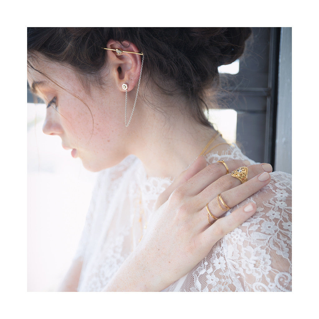 modern and sleek gold ear cuff bar with silver hanging chain worn by a beautiful girl in fine white lace