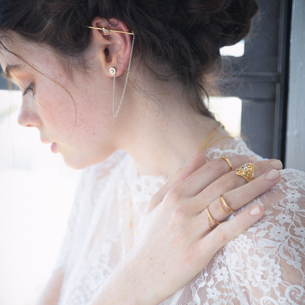 gold stacking chain rings worn with fine white lace sheer top and opal ear cuff bar earrings in gold and sterlign silver. beautiful jewellery for bridesmaid and great jewelry ideas for weddings