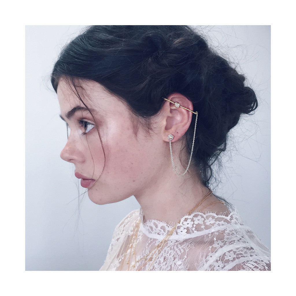 beautiful girl wearing gold ear cuff bar with white opal and silver dangling chain joined to an ear stud