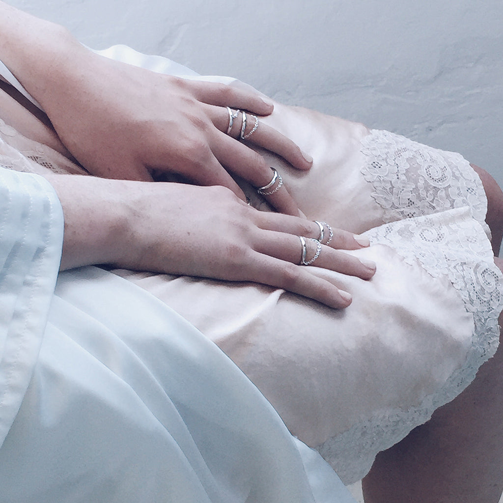 fine silver chain delicate rings worn with beautiful lingerie like a peach lace slip and white silk robe - sensual romantic and elegant - minimal and modern womens jewellery that is affordable and inexpensive. great as a valentine's gift or birthday gift for your girlfriend or wife.