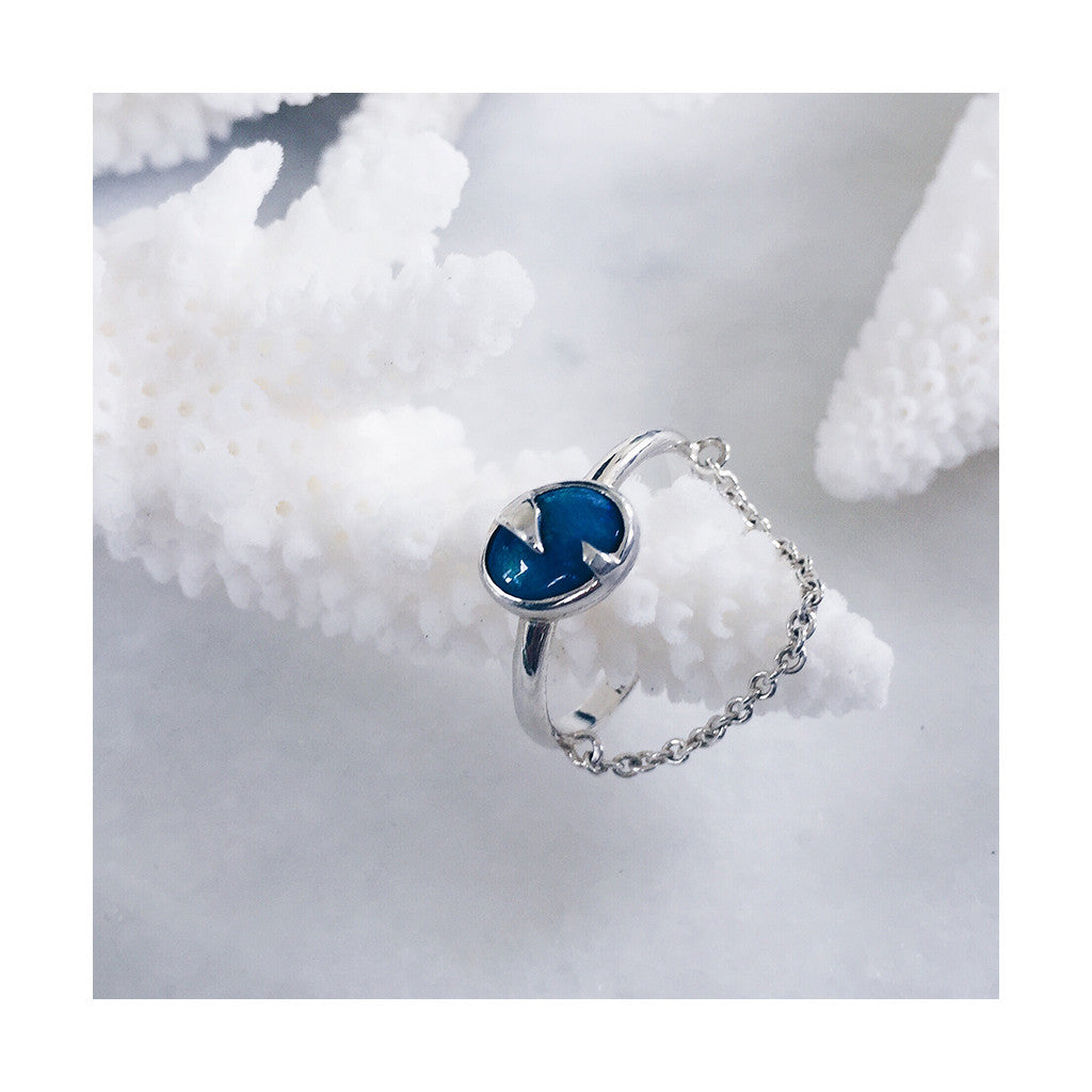 blue opal silver ring with fine dangling chain resting on white coral