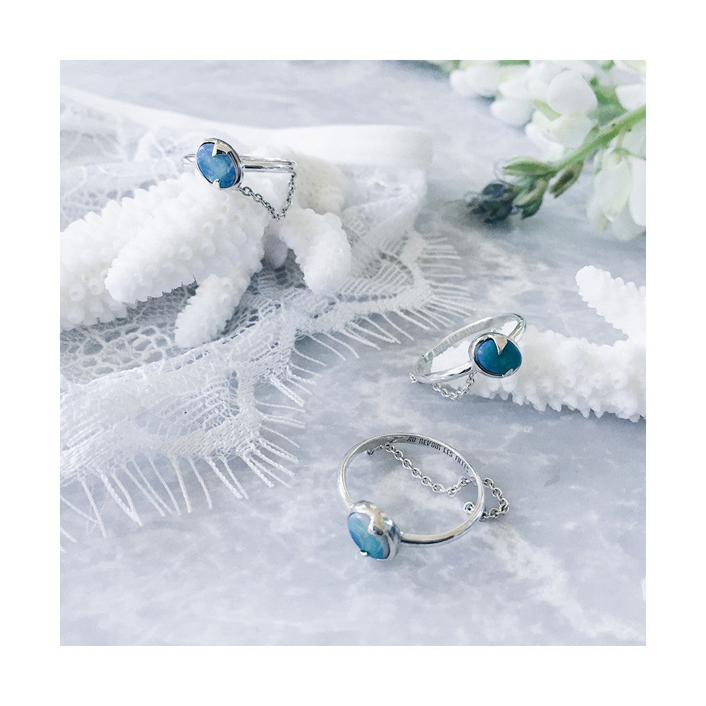 trio of modern blue opal silver rings with chain detail resting on white coral and lace