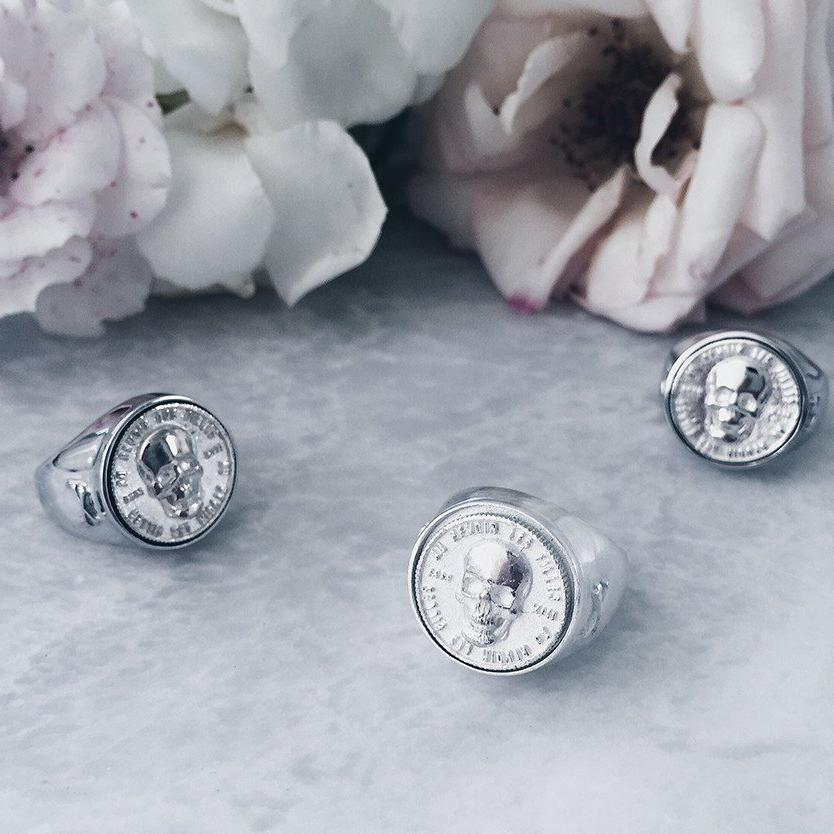 trio of silver skull signet rings against grey marble and faded roses