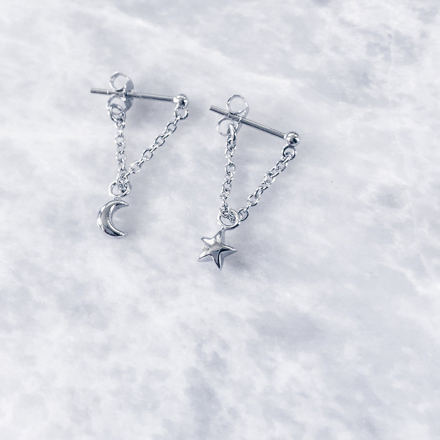 silver star moon dangling chain earrings on marble, love the grey colour tones and twilight romance