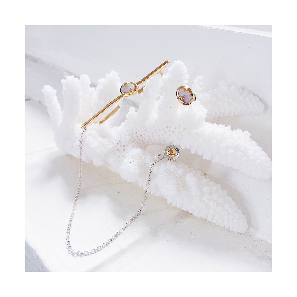 gold ear cuff bar with white pink opals joined by a fine silver chain to a bolt stud earring
