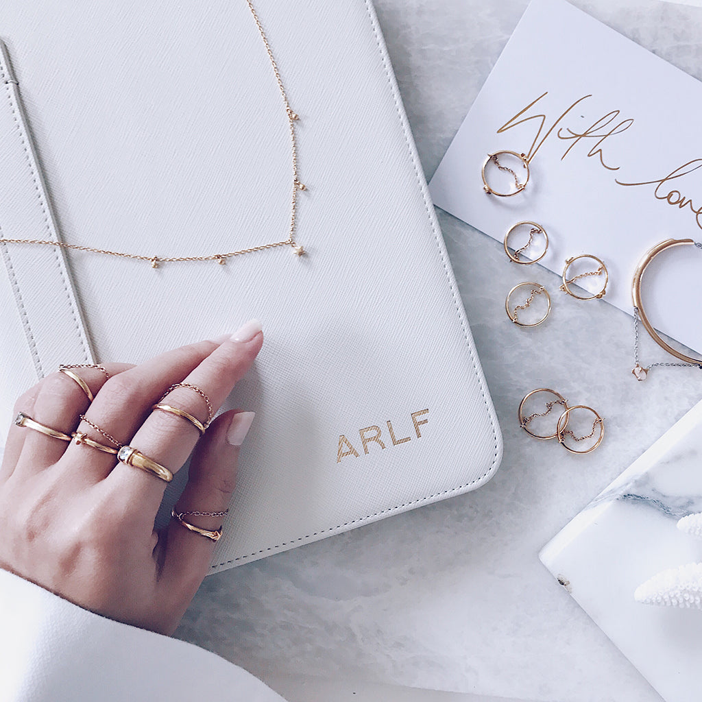 Flatlay of stacking gold rings, fine star necklaces in a modern white interior laid out with beautiful timeless marble. With love, perfect Xmas or Valentine Day's gift for her