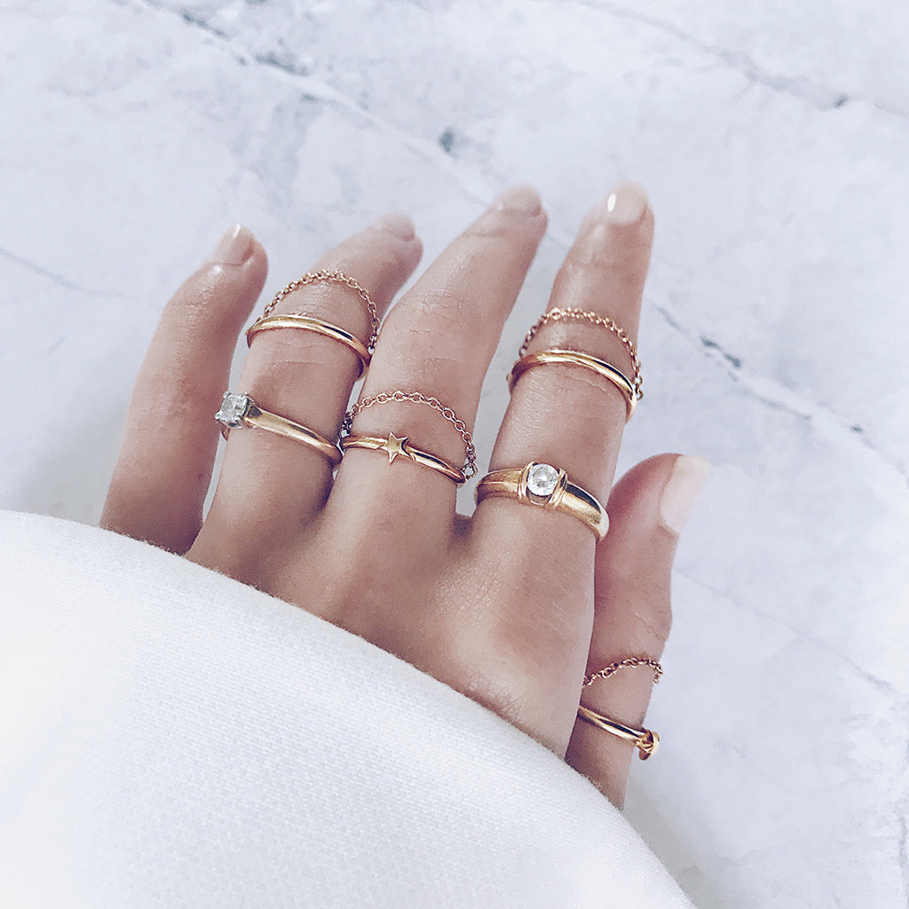 Fine stacking gold rings with modern chains that drape gracefully across the fingers - top jewelry trend - modern and minimal - womens gold ring jewellery