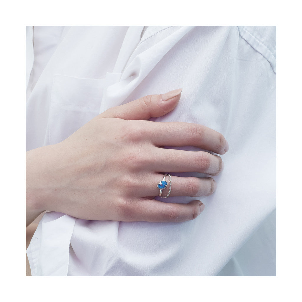blue opal silver ring with dangling chain worn with classic white shirt
