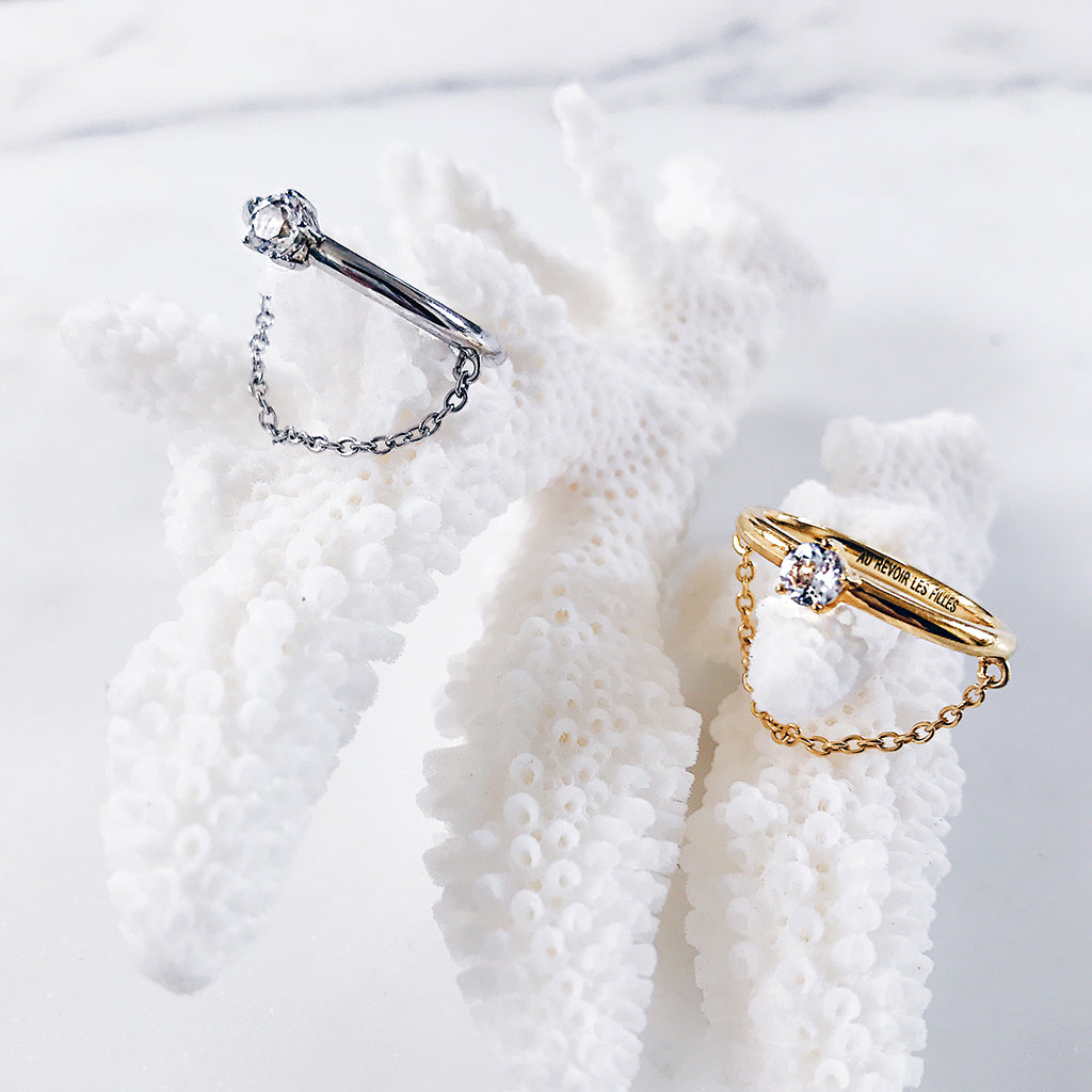brilliant affordable diamond chain rings in silver and gold resting on white coral - modern solitaire wedding ring design, perfect for engagement ring ideas