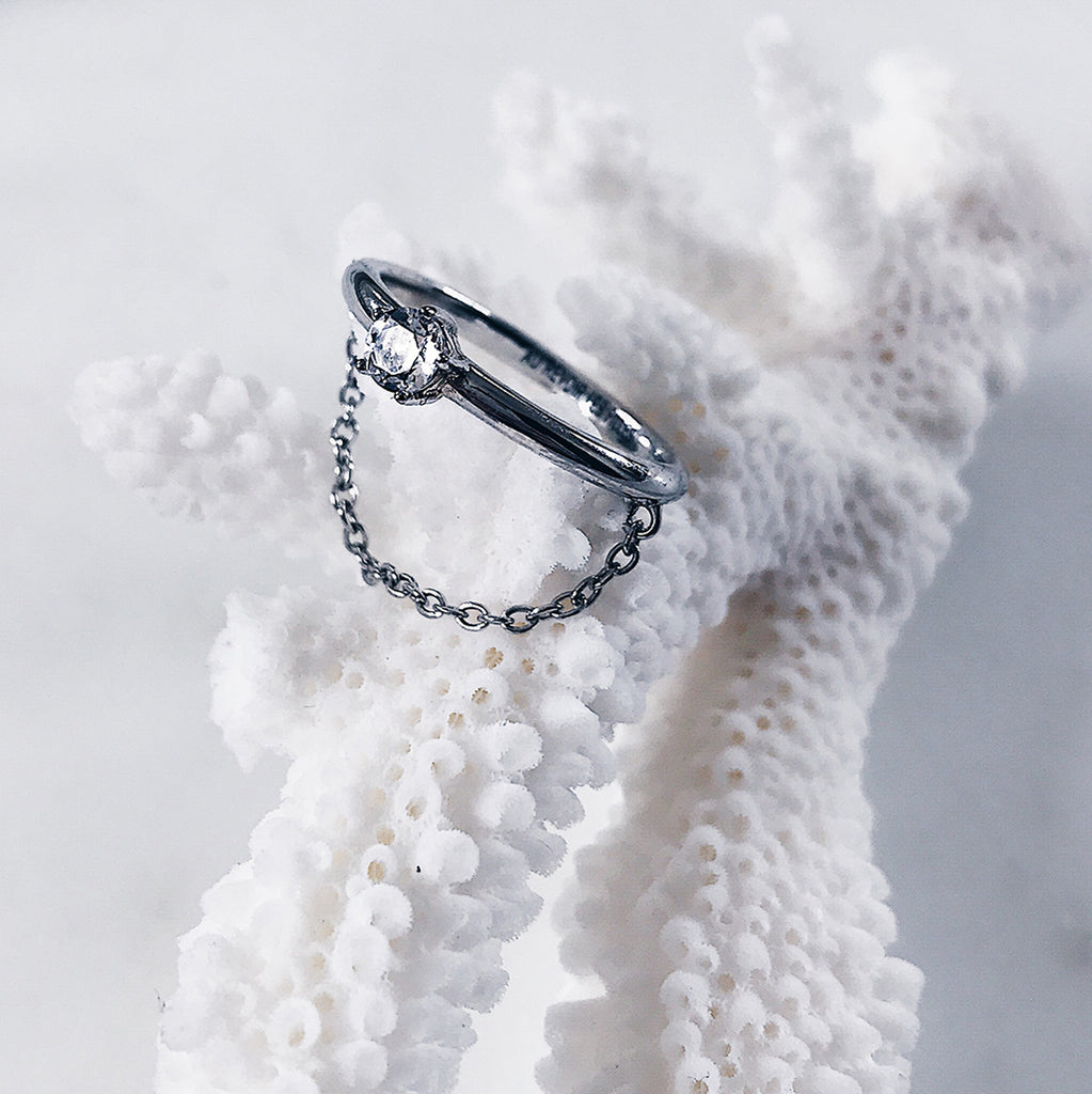 sparkly diamond ring on a classic thin band and fine chain resting on a white coral. chain drapes across the finger - modern, beautiful minimal silver solitaire ring for those who love minimalist jewelry