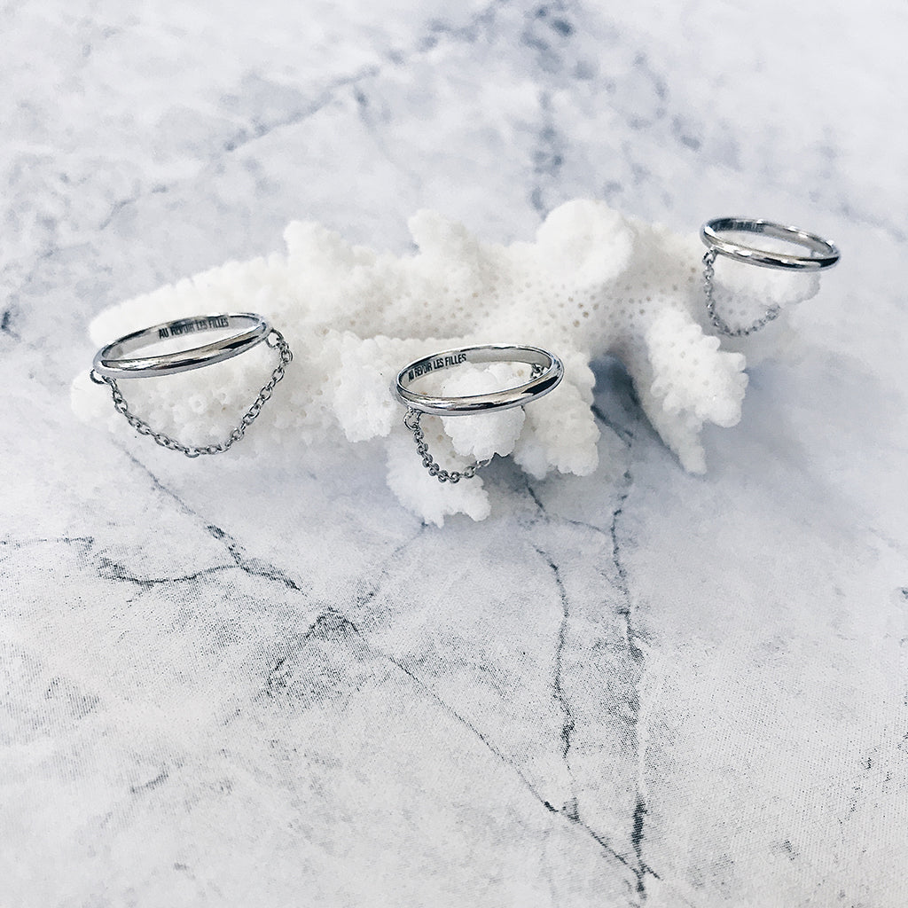 trio trinity of 3 three silver fine slim chain rings displayed on white coral and white grey marble - minimal monochrome aesthetic for women who love minimalist stacking rings and jewellery
