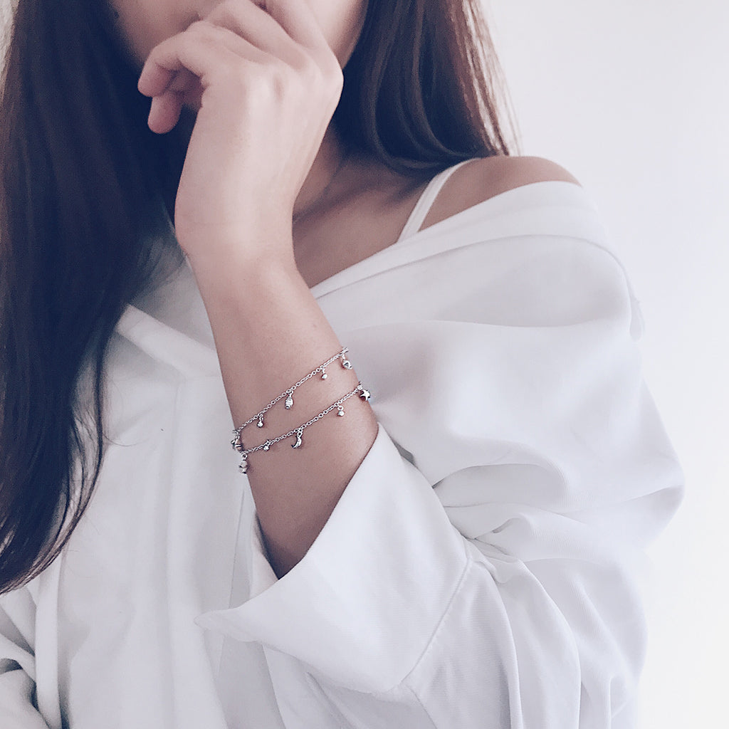 Layer fine bracelets with tiny star moon charms back with simple white shirt for an effortless chic minimal style - for those who love slim fine minimal bracelets that are trendy and timeless