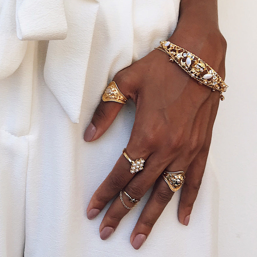 white cream outfit street style gold jewellery layered and stacked with skull star jewelry design