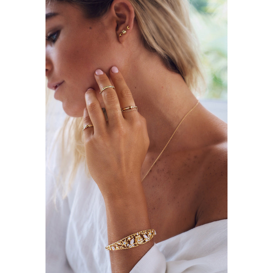 gold skull bangle bracelet worn with simple gold skull necklace and white sexy outfit