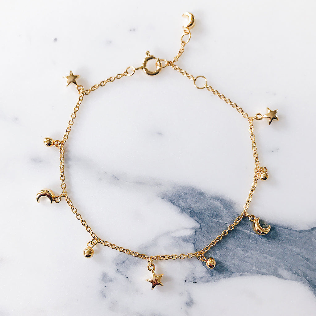 Star moon fine bracelet with tiny charms, beautifully displayed on white marble. Modern and gorgeous beautiful jewellery display, love the fine detailing and craftsmanship.