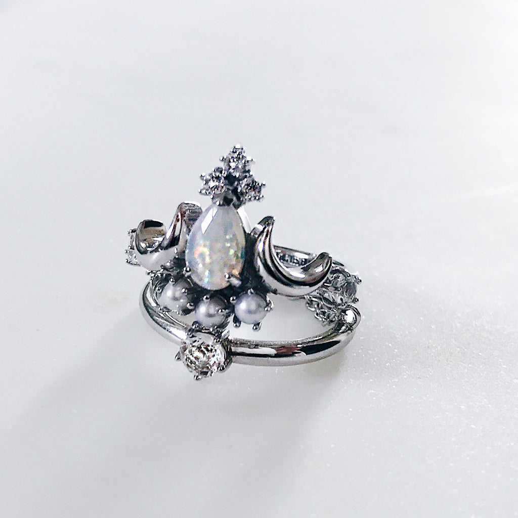 white opal ring in pear cut design with luminous cream pearls and sparkling white topaz flanked by twin crescent moons - beautiful cocktail silver ring in an antique heritage design resting on a diamond solitaire ring