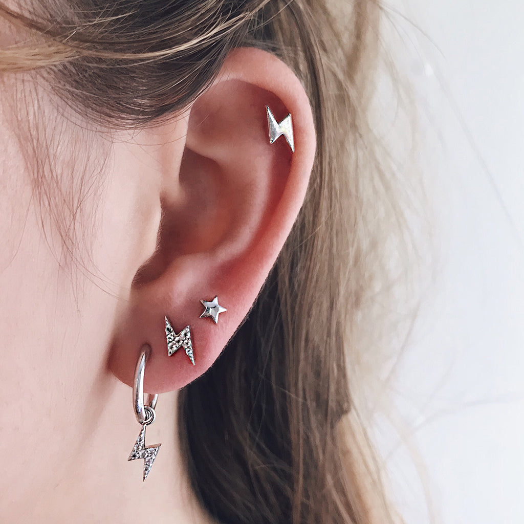 harry potter jewelry lightning bolt design sterling silver earrings ear hoops hanging from white coral white marble jewellery display. perfect for harry potter fan who loves wizards and witchcraft and magic. hypoallergenic, great for sensitive ears